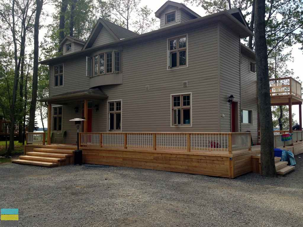 Two level cedar deck, skirt, cedar front porch, steps, landscaping, stone pebble driveway