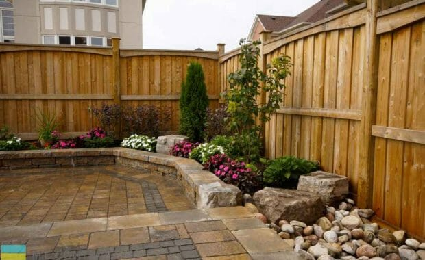 2 level interlock patio with retaining walls and large fence