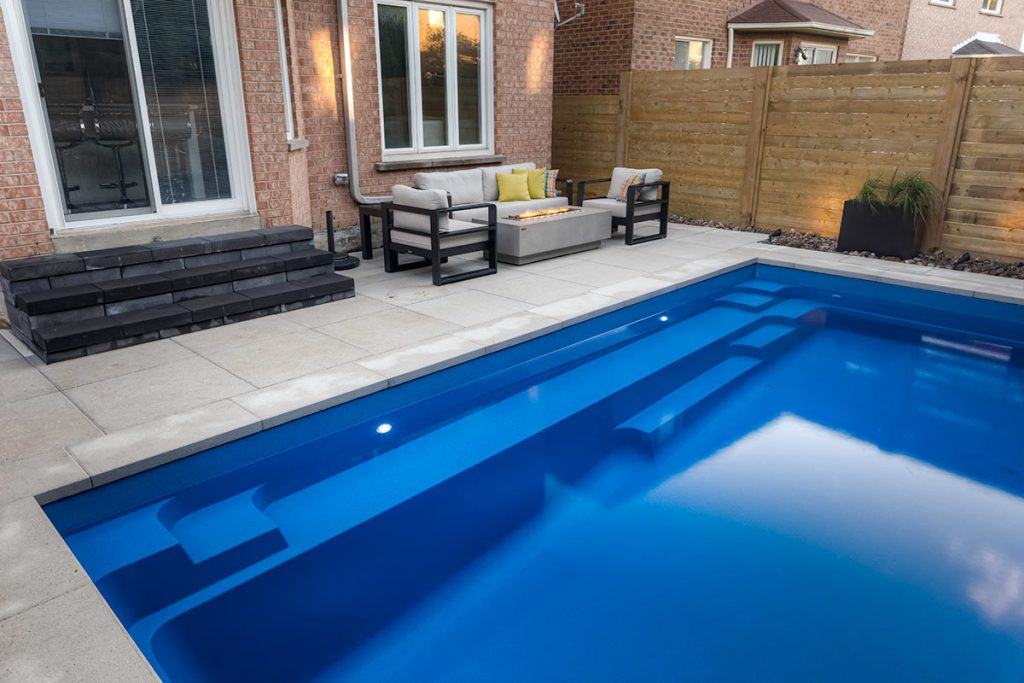 Complete Toronto Backyard Landscaping Project with Concrete Pool Installation, Outdoor Fireplace, Interlocking Patio & Privacy Fence