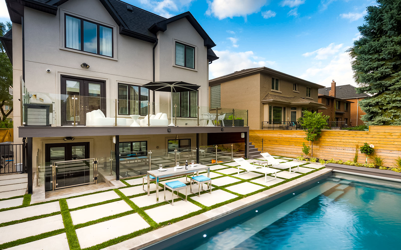 Complete Toronto Landscape Design Project in Nortown Toronto; Featuring Fiberglass Pool Installation, Pool Deck Interlocking & Decking, Outdoor Kitchen, Outdoor Fireplace, TREX Deck Build with Stainless Steel & Glass Railings by Toronto Landscaping Company.