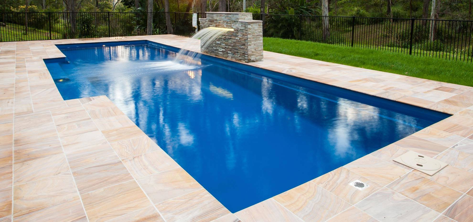 Elegance style fibreglass pool with coping and water feature by Leisure Pools