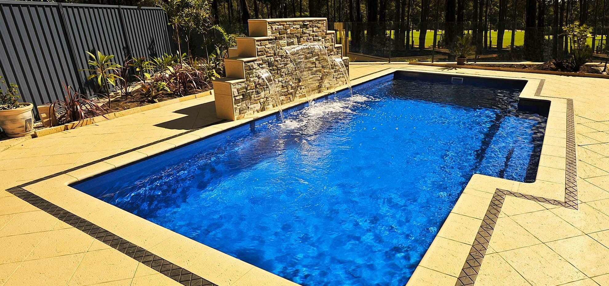 Elegance fibreglass pool design with stone water feature and coping by Leisure Pools