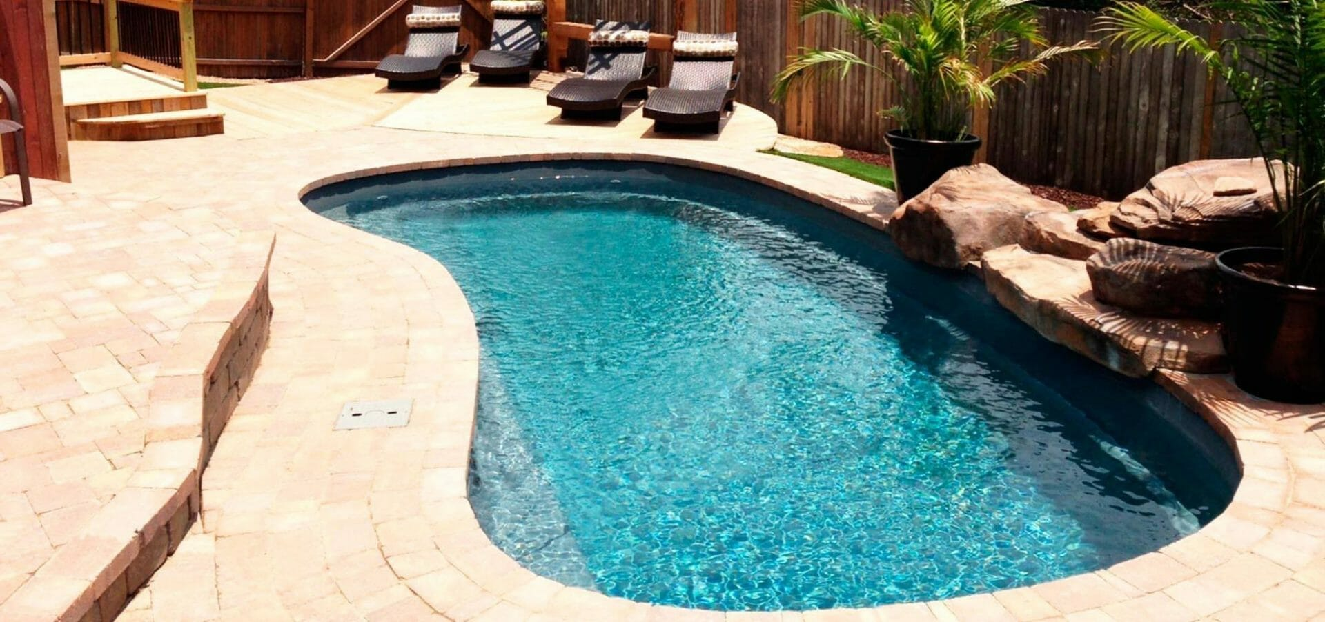 Tuscany Fibreglass Pool with armor stone and coping by Leisure Pools