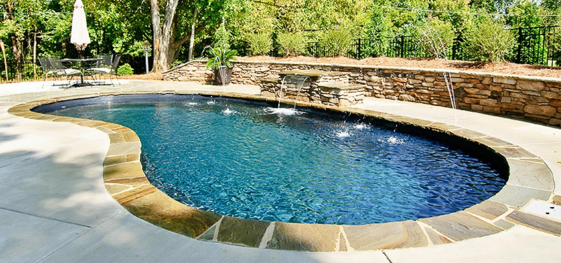Tuscany Fiberglass Pool with water feature, coping and retaining wall by Leisure Pools