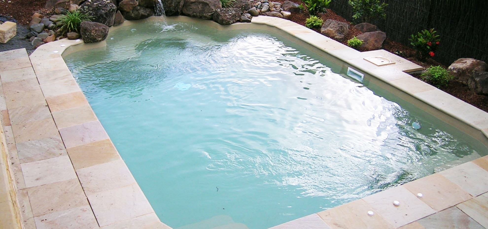 The Courtyard Roman fibreglass pool design with coping and water feature by Leisure Pools
