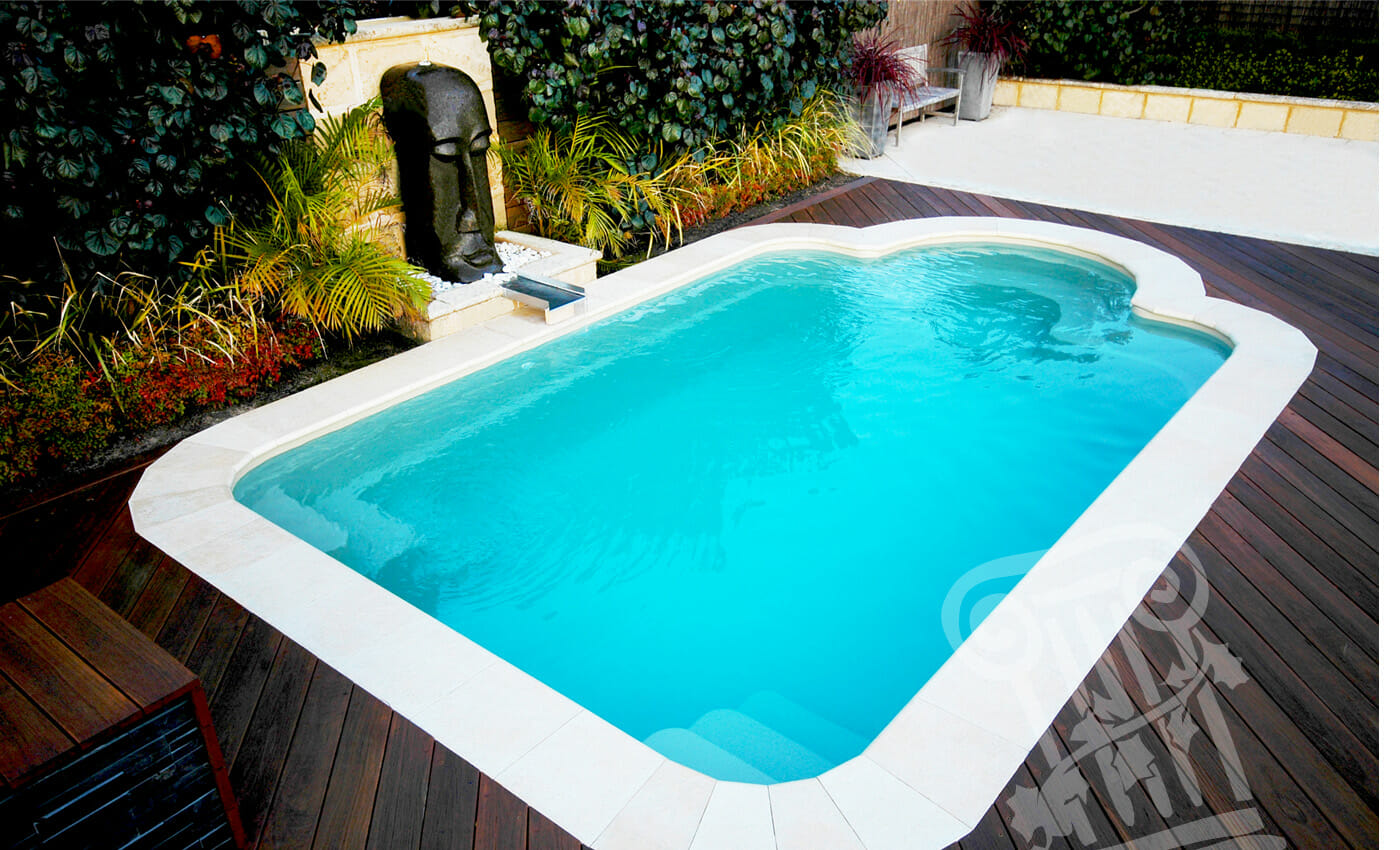 Fiberglass pool styled in Courtyard Roman design with water feature and coping by Leisure Pools
