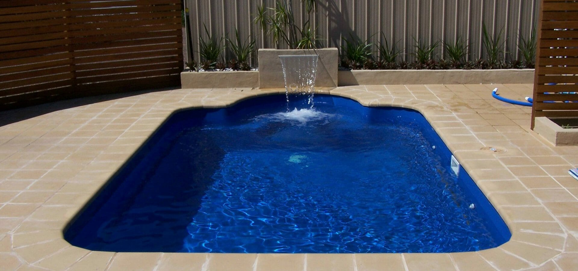 Courtyard Roman fibreglass pool design with water feature and coping by Leisure Pools