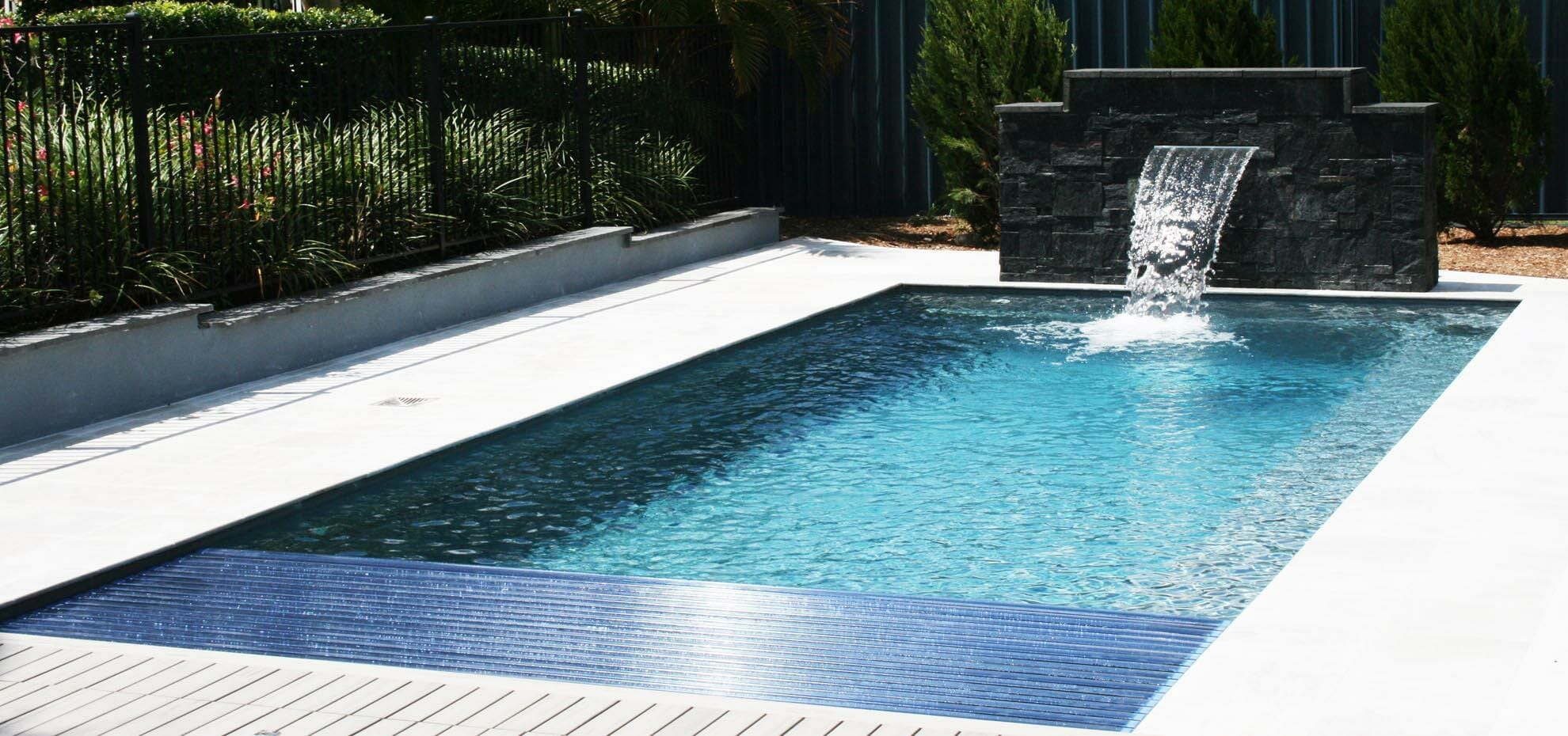 Reflection fibreglass pool with Auto Cover feature, as well as water feature by Leisure Pools