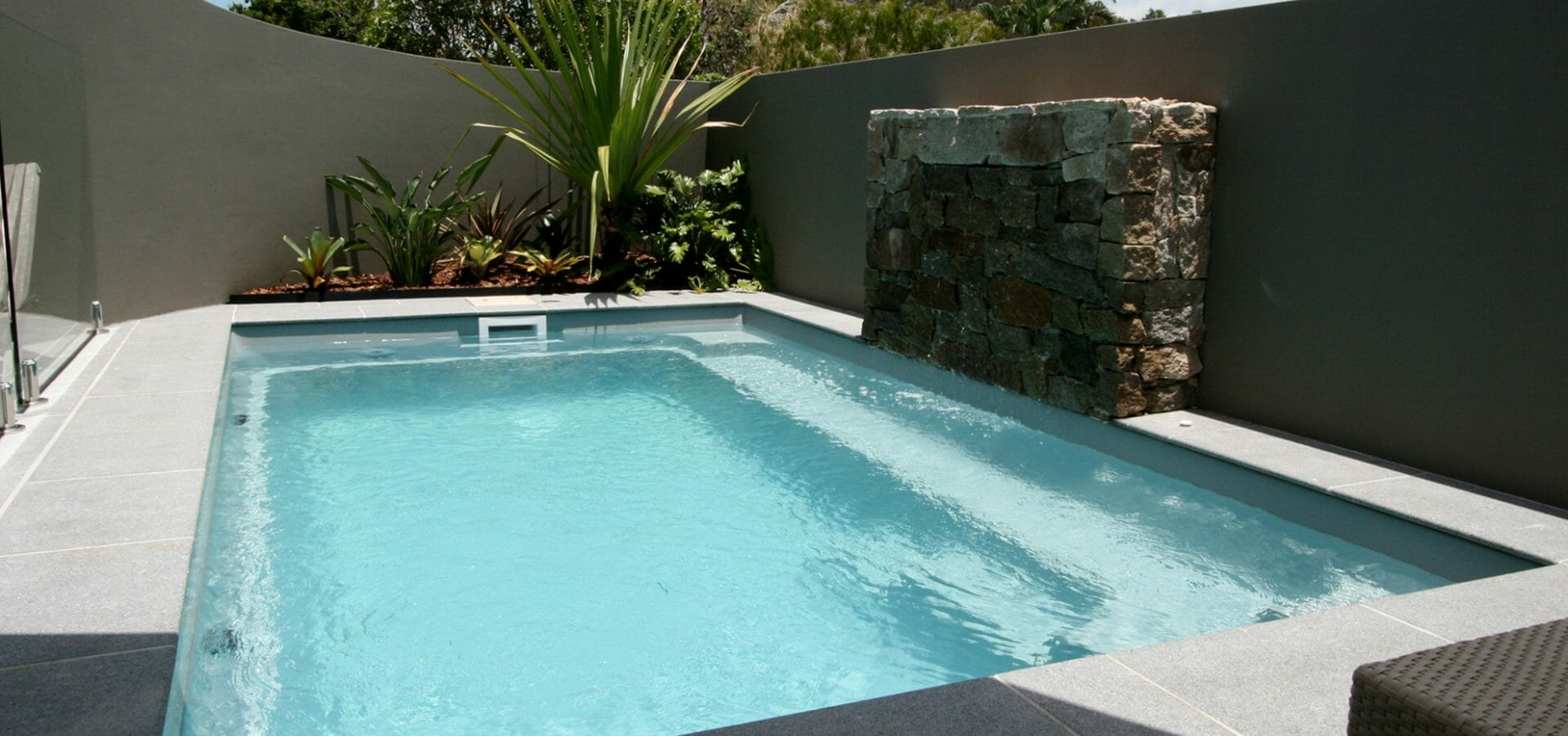 Rectangular shaped Harmony fibreglass pool with coping and water feature by Leisure Pools