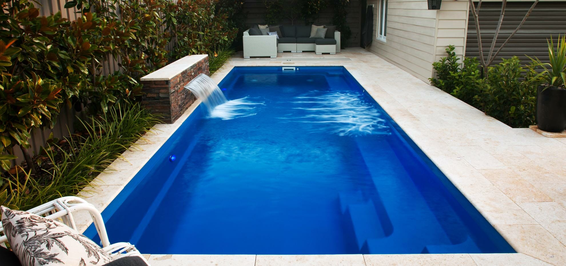Rectangular harmony fibreglass pool with coping and water feature by Leisure Pools