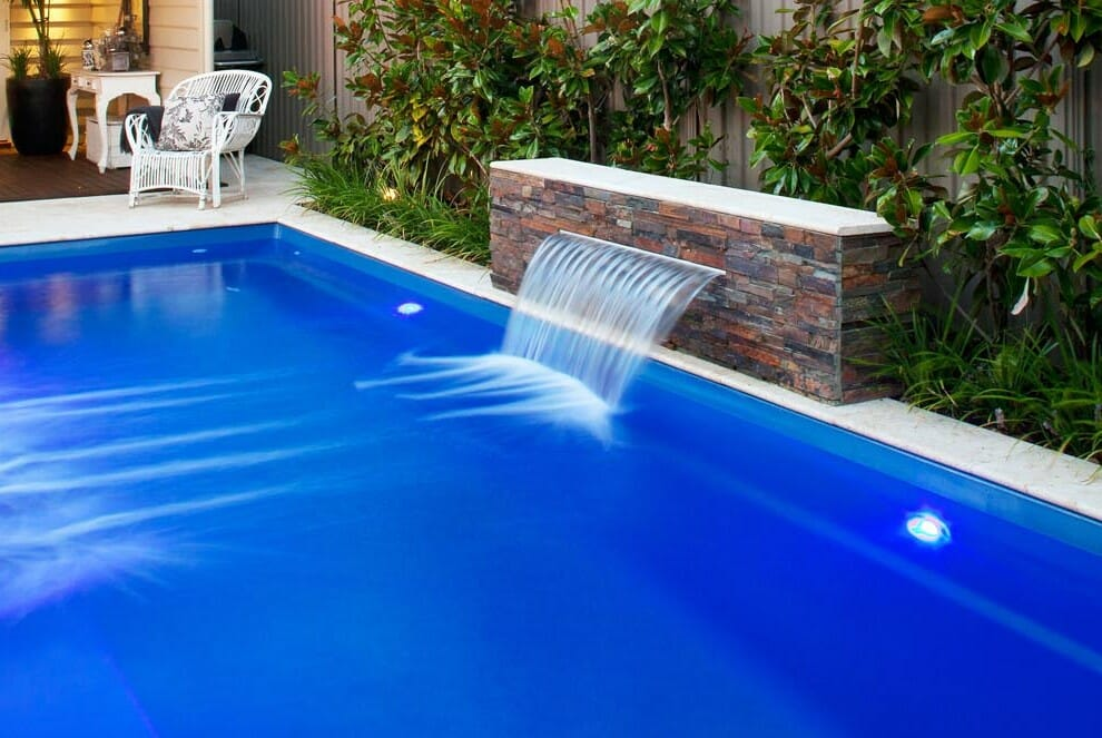 Rectangular Harmony Fibreglass Pool with water feature and coping by Leisure Pools