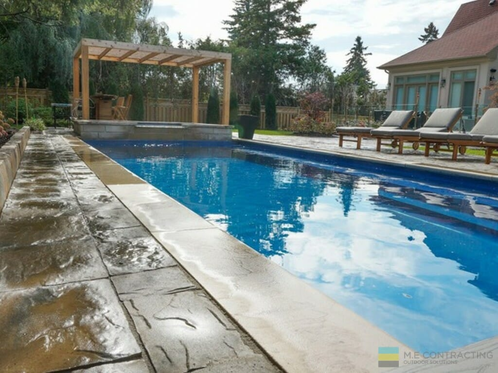 Landscaping project with fiberglass pool, interlocking patio, cedar deck, pergola, and fence, tempered glass railings with stainless steel posts and clips
