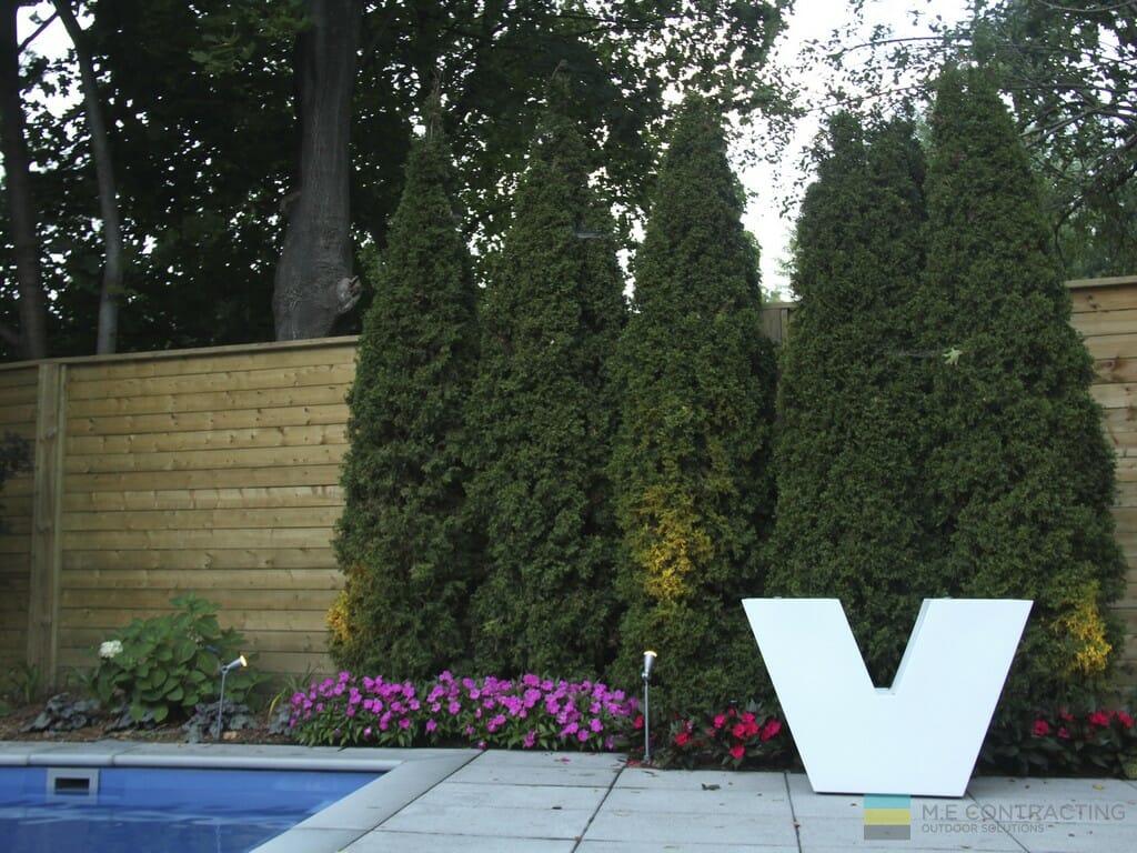 Landscaping, stone patio, fiberglass pool, cedar fence, and Vondom furniture