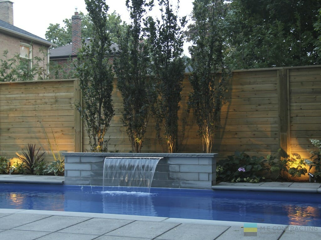 Fiberglass pool, stone patio, cedar fence, landscaping