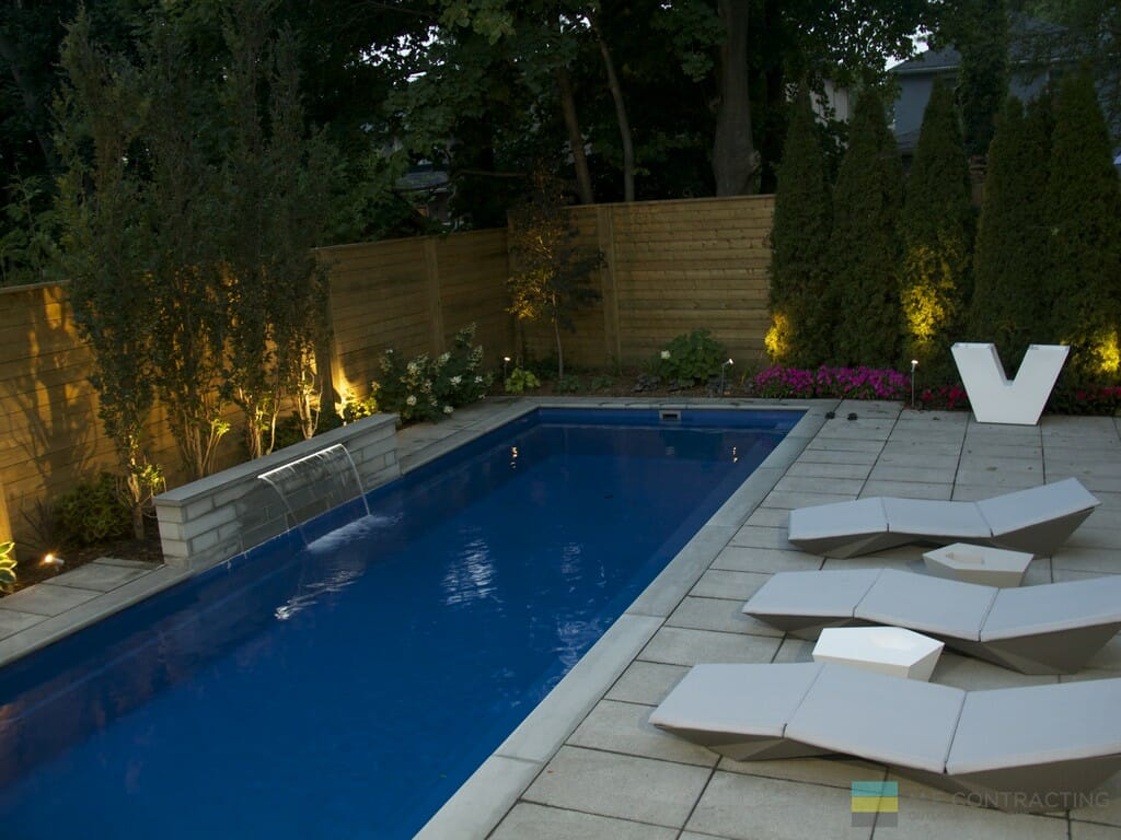Fiberglass pool, stone patio, cedar fence, landscaping and stone fountain.