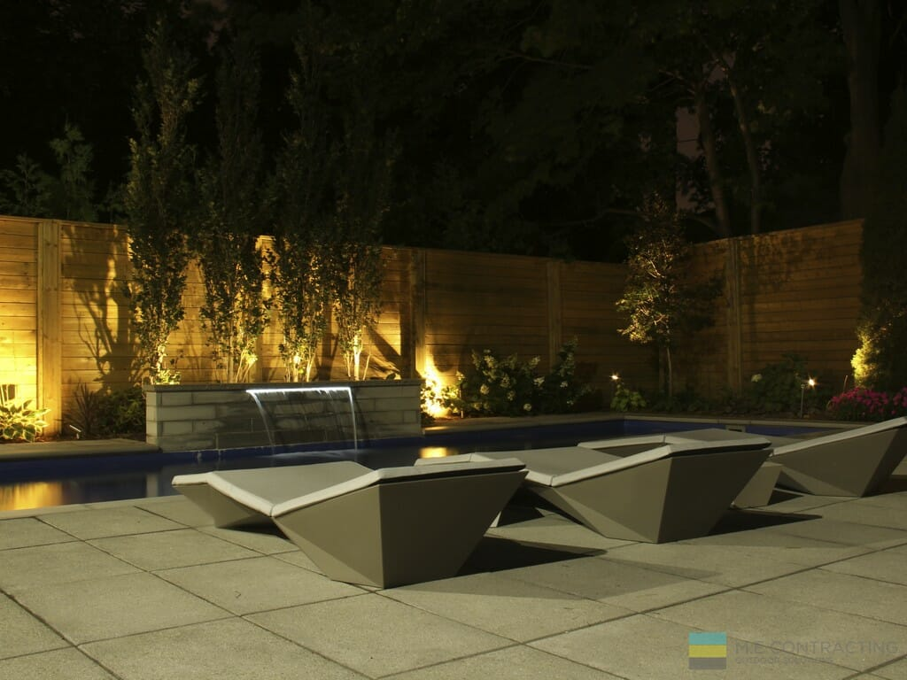 Fiberglass pool, stone patio, cedar fence, landscaping, and outdoor furniture.