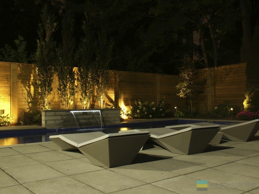 Fiberglass pool, stone patio, cedar fence, landscaping, and outdoor furniture.
