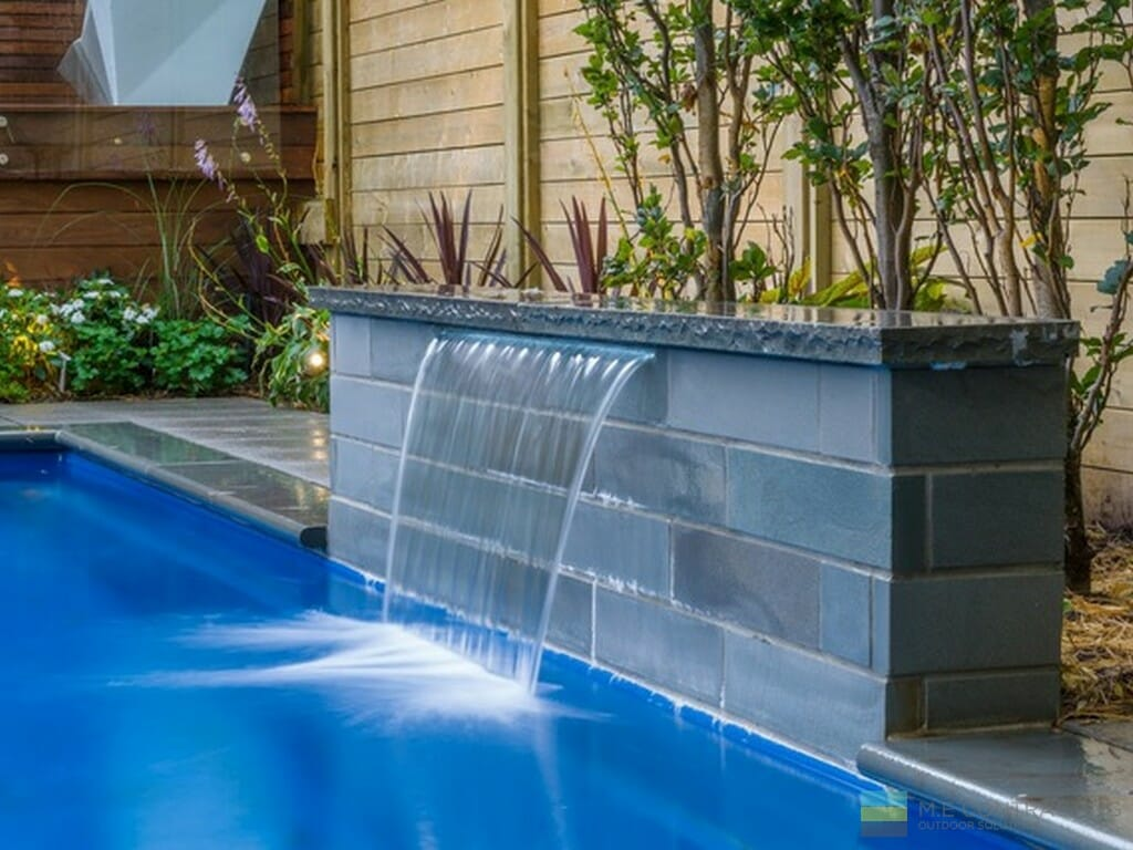 Landscaping with fiberglass pool, stone fountain, and cedar fence