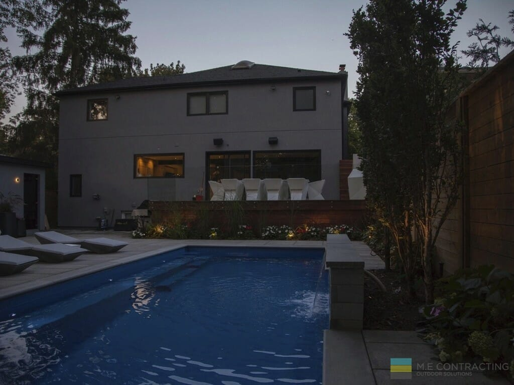 Landscaping with fiberglass pool, stone patio and IPE deck with frame-less glass railings.