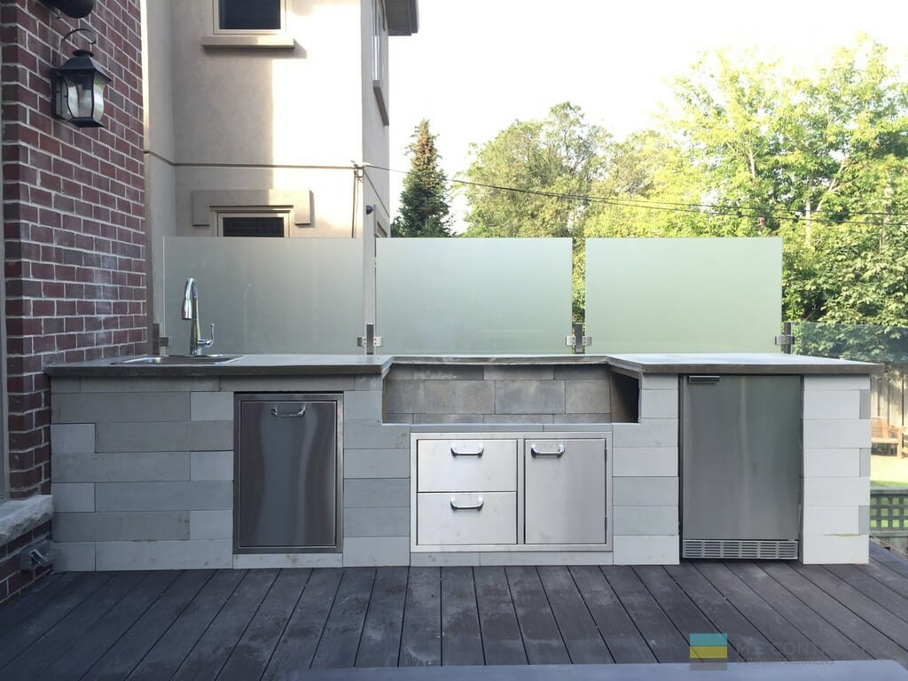 M.E. Contracting outdoor kitchen, stone veneer, frosted glass privacy wall, stone counter tops, stainless steel clips, PVC deck
