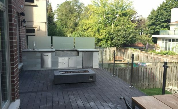 Landscaping, outdoor kitchen, PVC deck, frosted glass privacy wall, fire pit