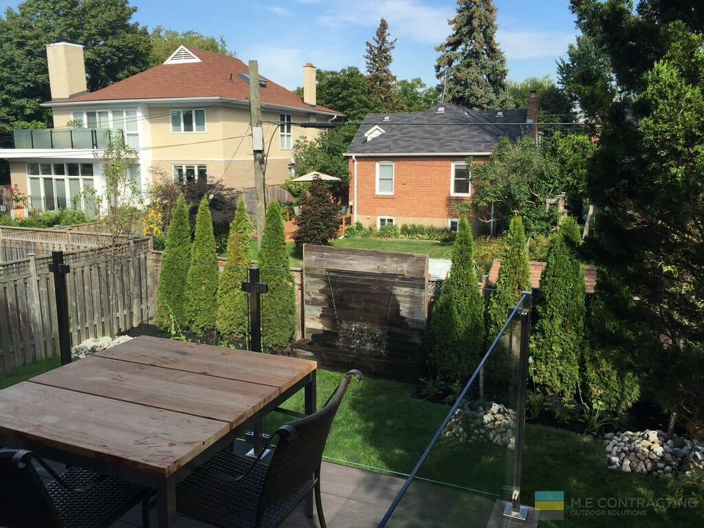Landscaping with water feature, PVC deck, tempered glass railings with stainless steel posts and clips