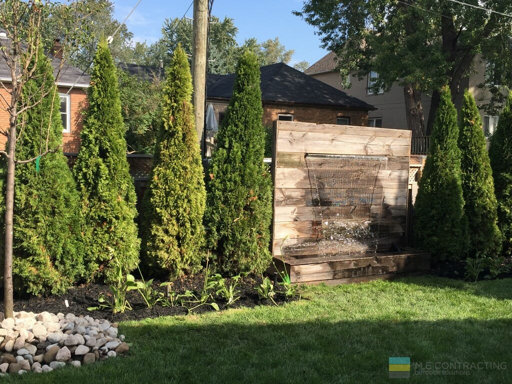 Landscaping with water feature attached to cedar privacy fence