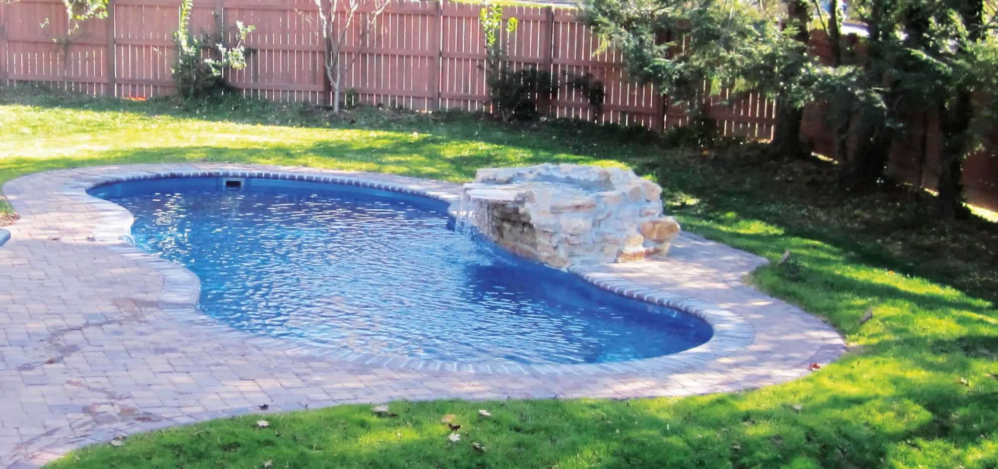 Mediterranean fibreglass pool with water feature by Leisure Pools