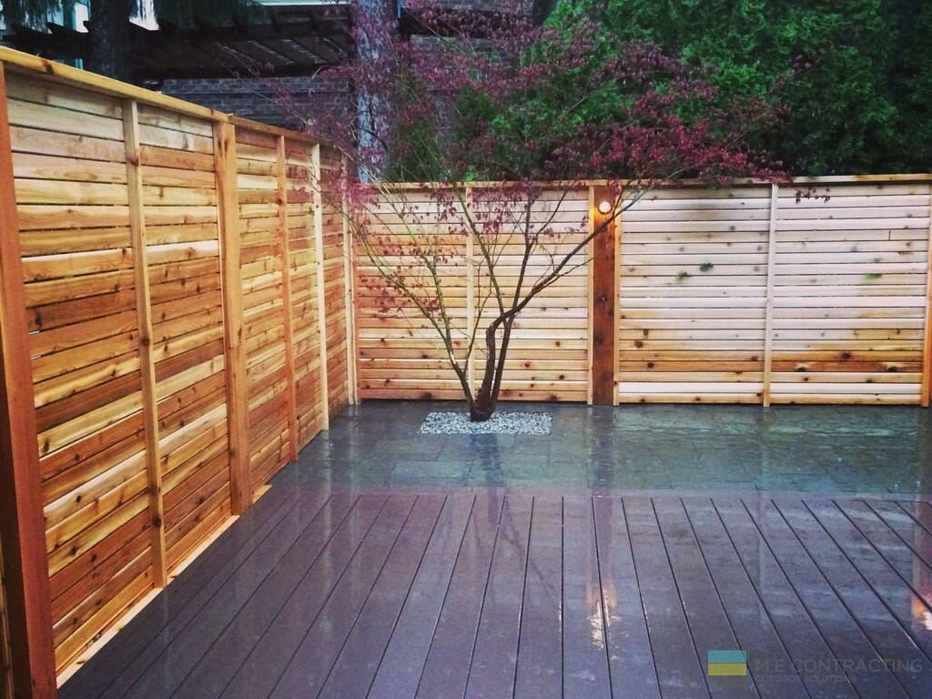 Patio stone, PVC deck, and cedar fence