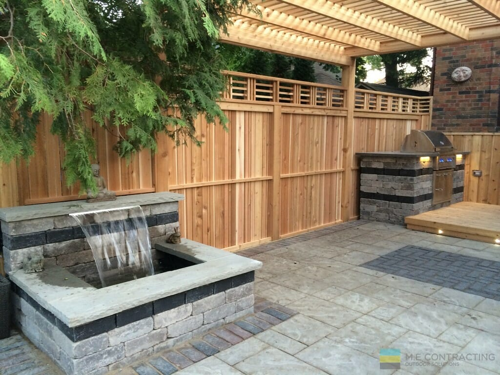 Outdoor kitchen, interlocking patio waterfall and cedar fence