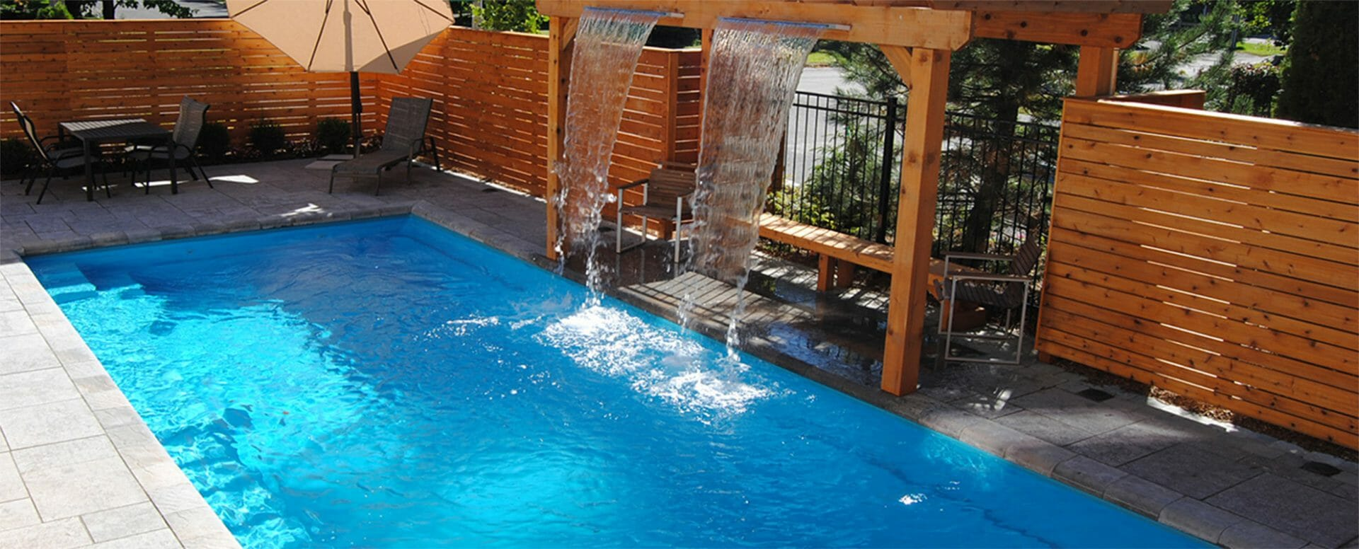 Fibreglass pool with water feature, coping, and cedar pergola and fence by Leisure Pools