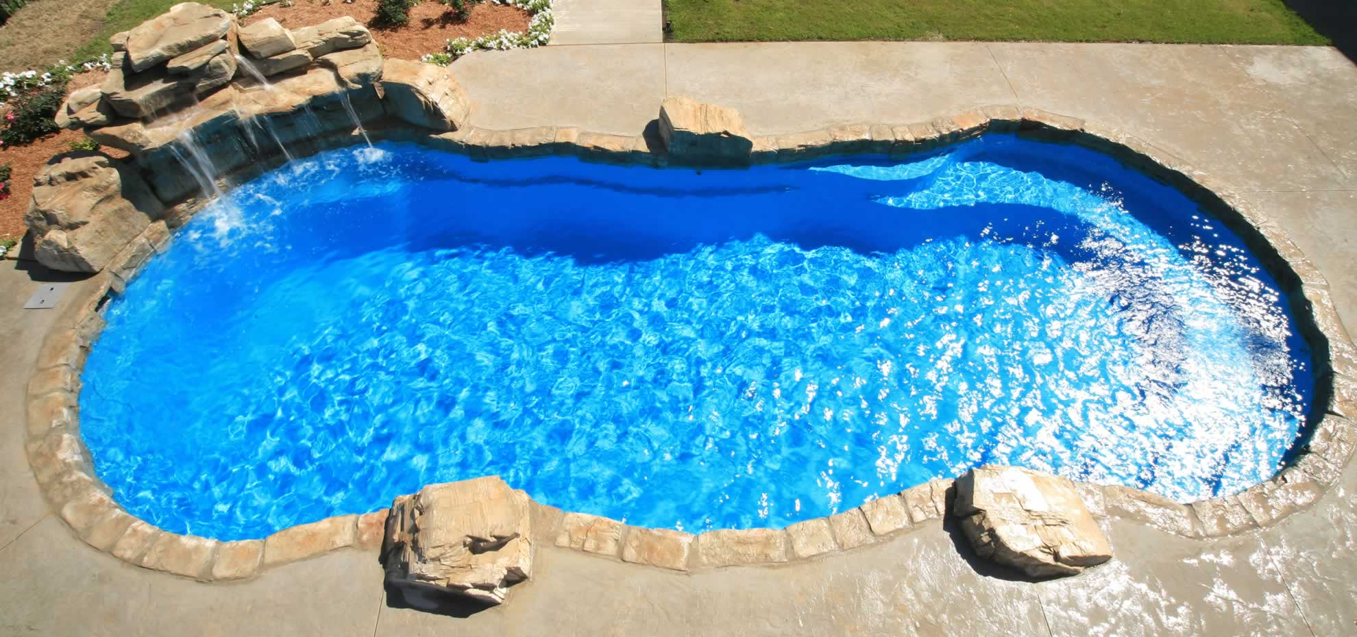Fiberglass pool with coping and water feature by Leisure Pools