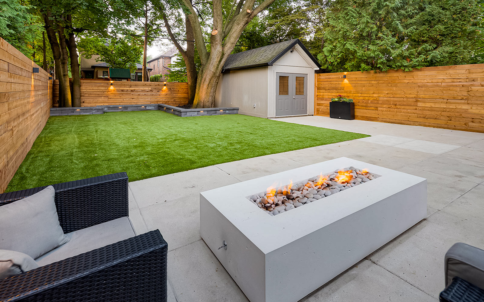 Complete Toronto Landscaping Project; Featuring Small Retaining Wall, Composite Deck Build with Stainless Steel Glass Railings, Interlocking & Outdoor Fireplace by Toronto Landscaping Company.