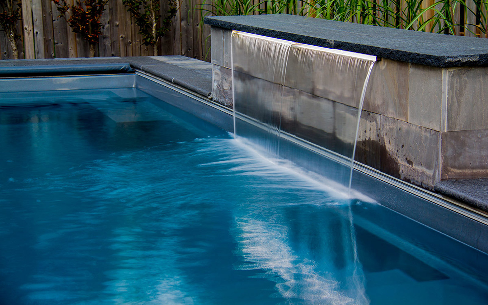 Small Toronto Fiberglass Pool Installation With Water Feature by Toronto Landscaping Company.