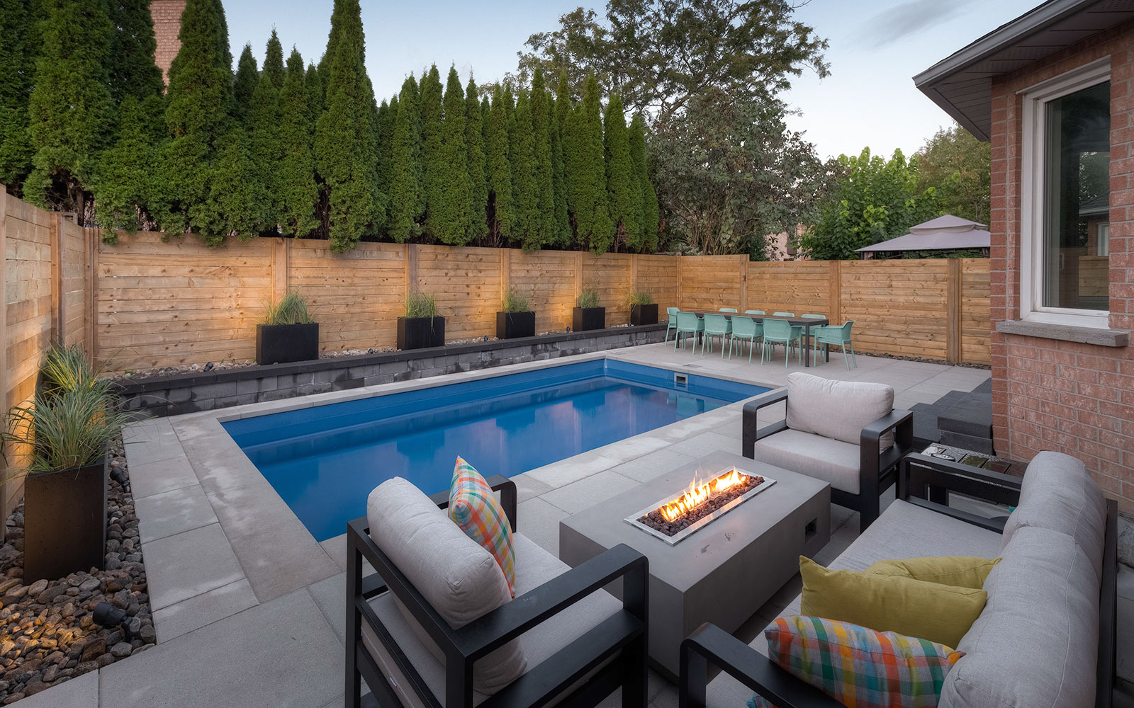 Toronto Landscape Project; Featuring Concrete Pool Installation, Cedar Privacy Fence, Outdoor Fireplace, Pool Deck Interlocking & Small Retaining Wall Around Pool Area by Toronto Landscaping Company.