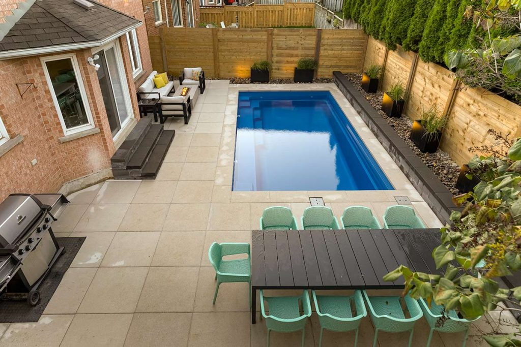 Toronto Landscaping Project for Small Toronto Backyard; Featuring Concrete Pool Installation, Interlocking, Outdoor Fireplace, Cedar Privacy Fence & Retaining Wall