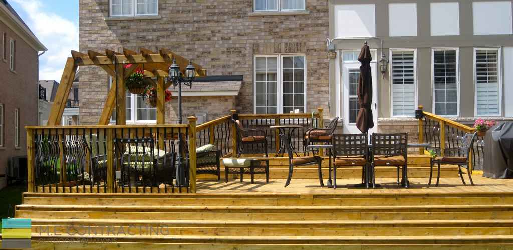 Pressure treated deck with pergola, stone veneer, pressure treated frame railings with aluminum