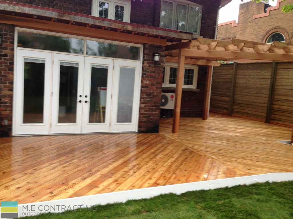 Cedar and pressure treated deck with pergola, landscaping, stone veneer and cedar fence with gate