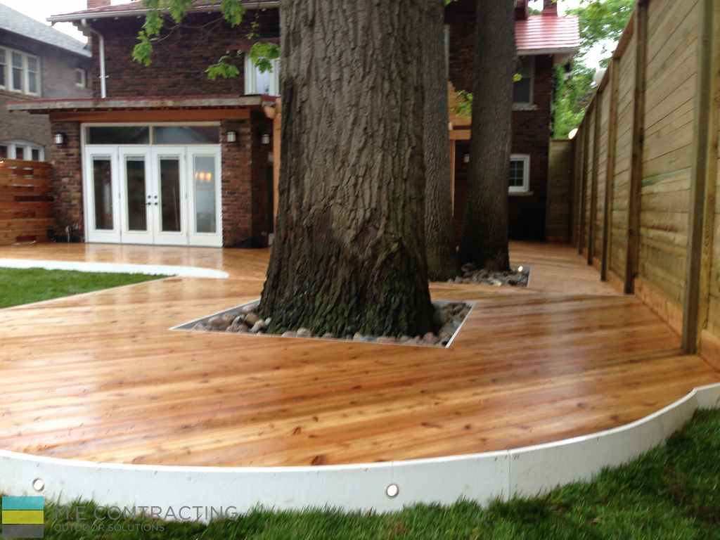 Cedar and pressure treated deck with pergola, landscaping and stone veneer and cedar fence