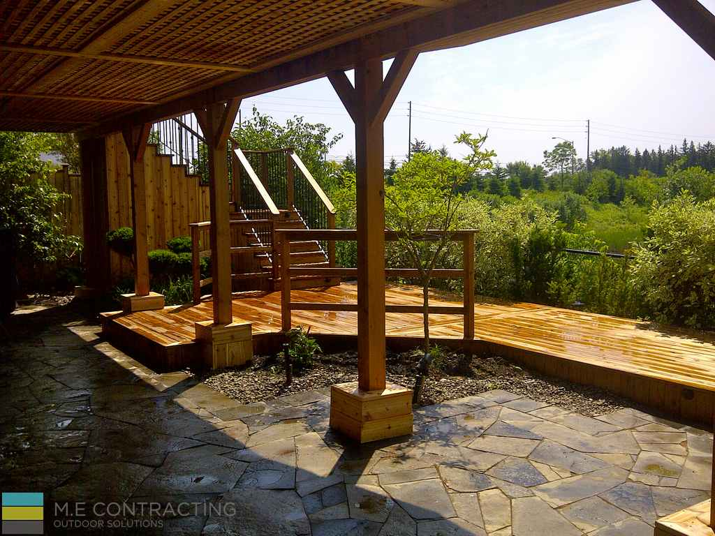 Pressure treated and cedar deck with, stone veneer, pressure treated frame railings with aluminum, and landscaping, interlocking basement walkout