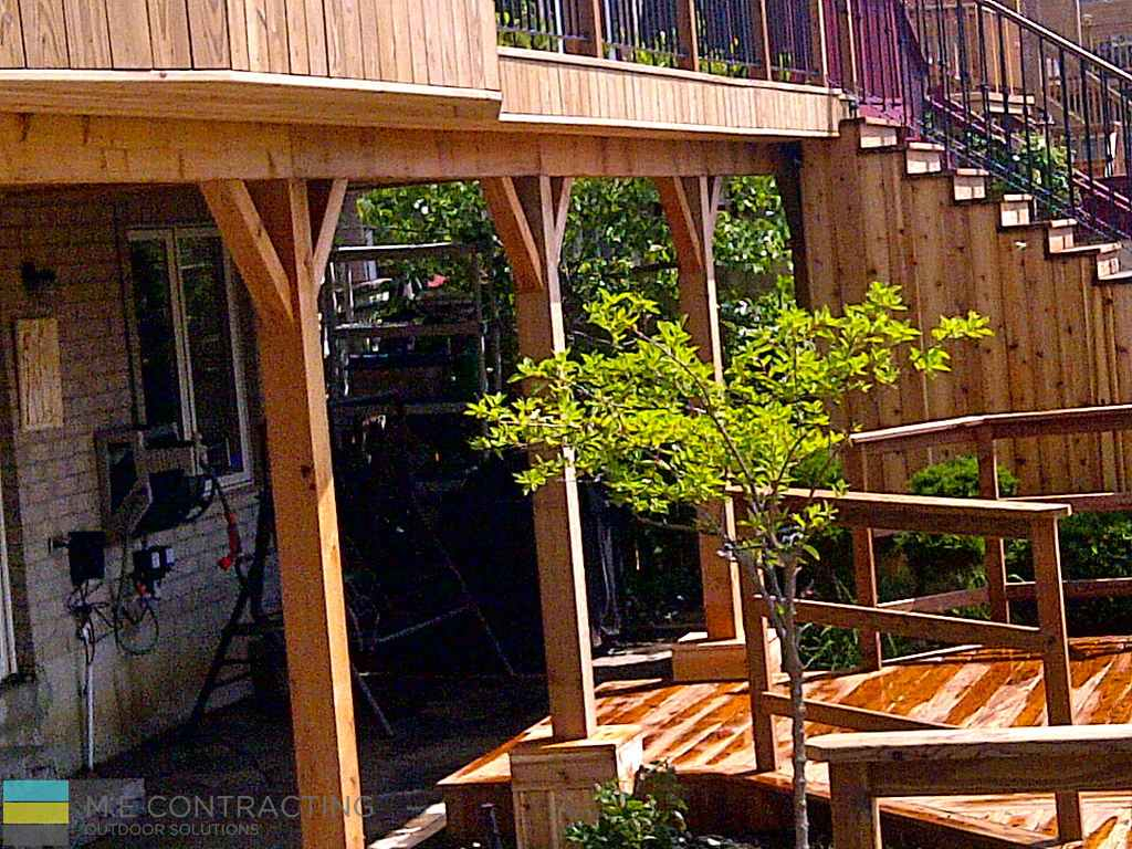 Pressure treated and cedar deck with, stone veneer, pressure treated frame railings with aluminum, and landscaping, interlocking