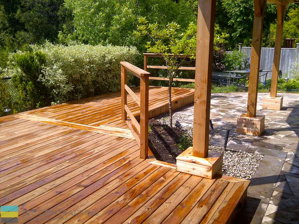 Pressure treated deck with pergola, stone veneer, pressure treated frame railings with aluminum, and landscaping, interlocking