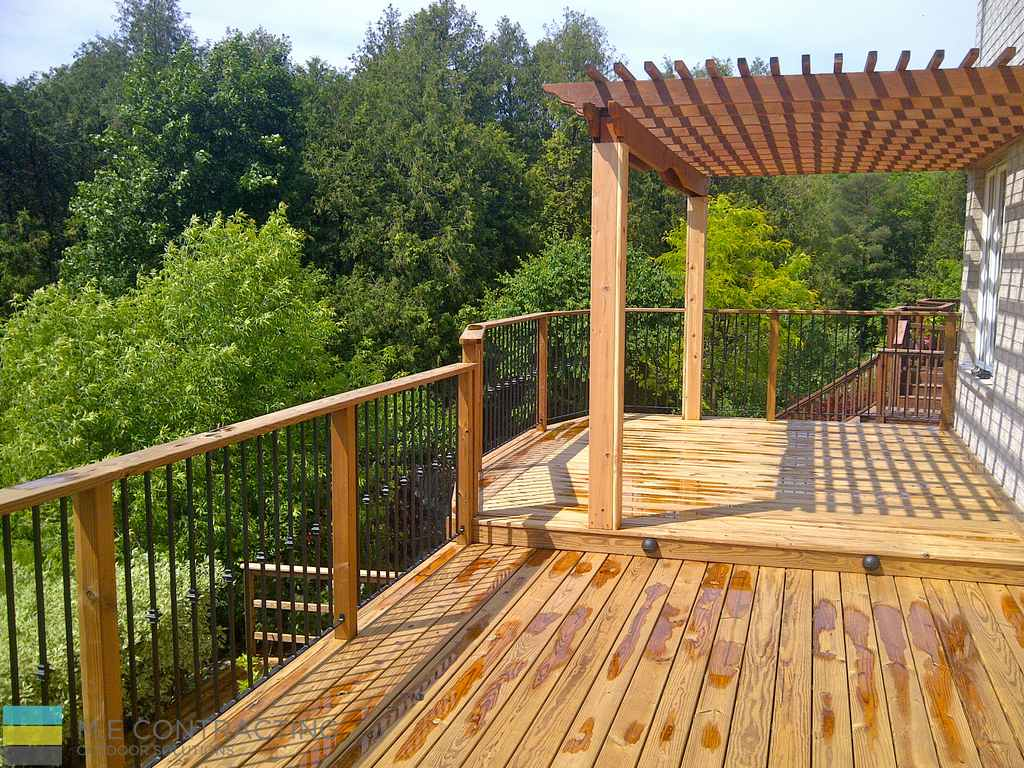 Pressure treated deck with pergola, stone veneer, pressure treated frame railings with aluminum, and landscaping