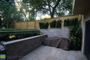 Landscaping, Stone retaining wall, interlocking patio, cedar fence, basement walkout