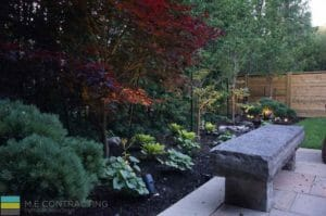 Landscaping, fire pit, interlocking patio, stone bench, lighting, and cedar fence