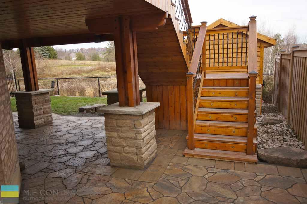Pressure treated deck and steps, interlocking patio, stone veneer, stone pebbles and cedar fence.