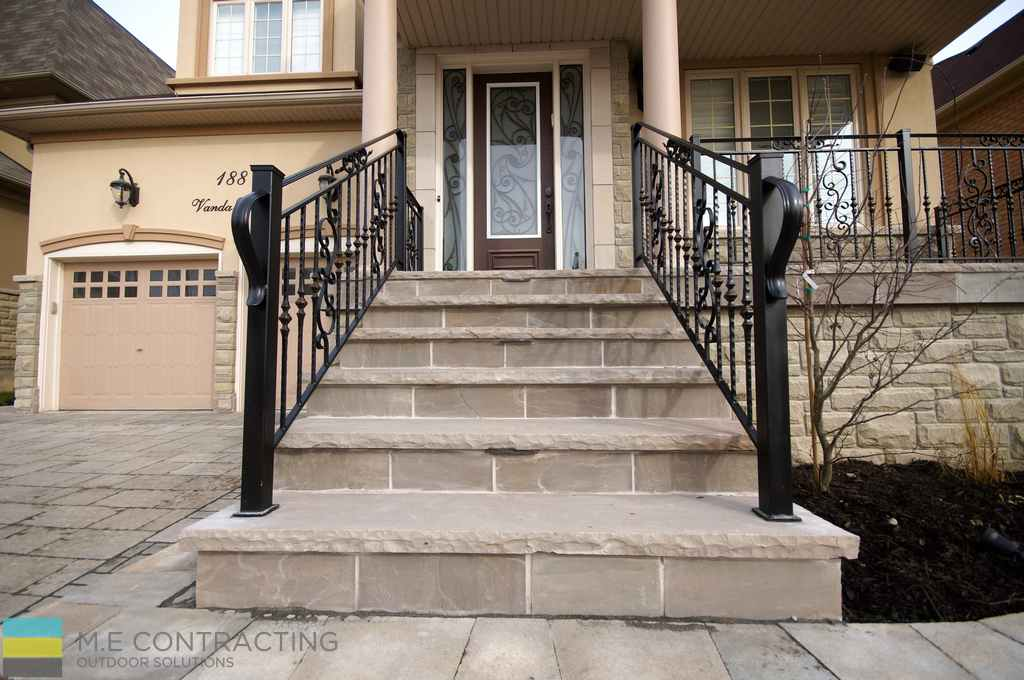 Landscaping, interlocking driveway, retaining wall with stone pebbles, stone porch with aluminum railings