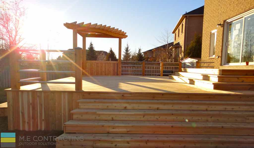 Cedar deck with skirt, light luminated caps, stainless steel fence with cedar posts, landscaping