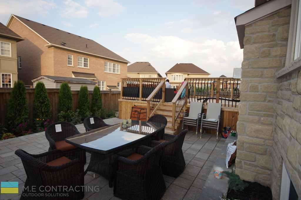 Cedar deck, aluminum railings with cedar posts and frames, interlocking patio, outdoor furniture, stone veneer