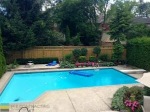 M.E. Contracting project with a fiberglass pool, interlocking stone patio and landscaped yard, privacy screen